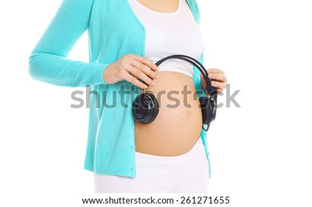 Pregnant woman and headphones on a white background - stock photo