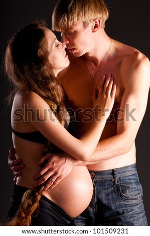 pregnant woman and her man on black background
