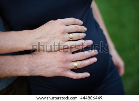 Pregnant woman and husband holding hands on belly - stock photo
