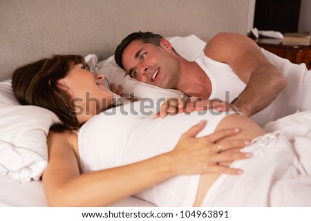Pregnant woman and husband in bed - stock photo