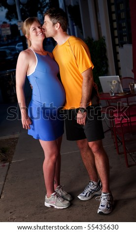 Pregnant woman and husband in fitness attire on the street - stock photo