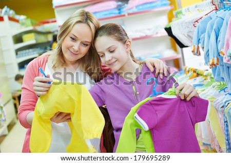 pregnant woman and little girl choosing newborn baby clothes during shopping at garments supermarket - stock photo