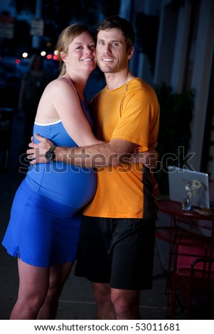 Pregnant woman and man in fitness attire on the street - stock photo