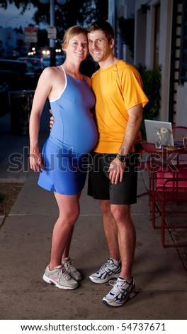 Pregnant woman and partner in fitness clothing posing on the sidewalk - stock photo