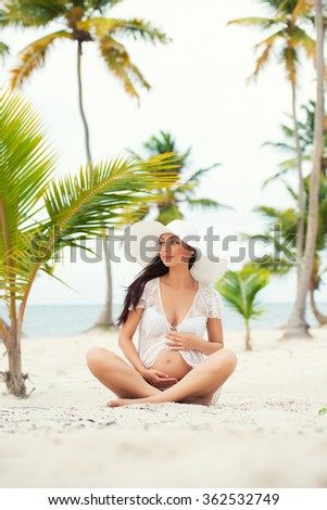 Pregnant woman and Travel. Rest in exotic countries. Sea, beach, palm trees. - stock photo