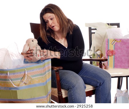 Pregnant woman at a baby shower admiring a gift.  Isolated on white. - stock photo