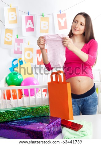 Pregnant woman at her baby shower event looking at pink body for a girl - stock photo