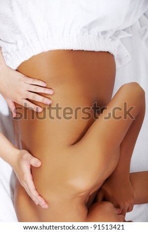 Pregnant woman being wrapped with a towel, lying on a bed and having a massage. - stock photo