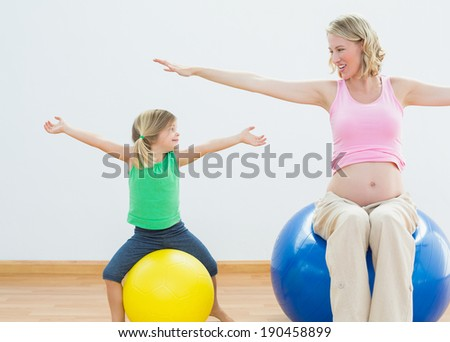 Pregnant woman bouncing on exercise ball with young daughter in a fitness studio - stock photo