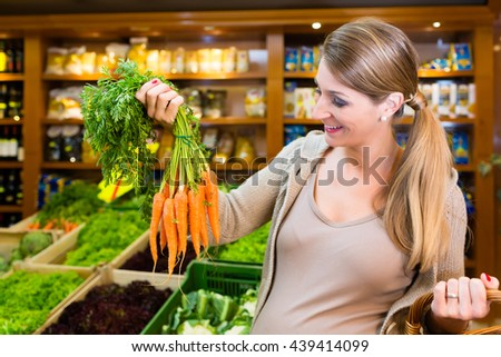 Pregnant woman buying healthy vegetables in grocer store - stock photo