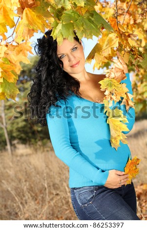 pregnant woman caressing her belly over autumn park, outdoors