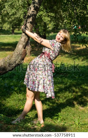 Pregnant woman clinging to a tree trunk in the Park Sunny summer day