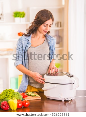 Pregnant woman cooking salad in the kitchen at home