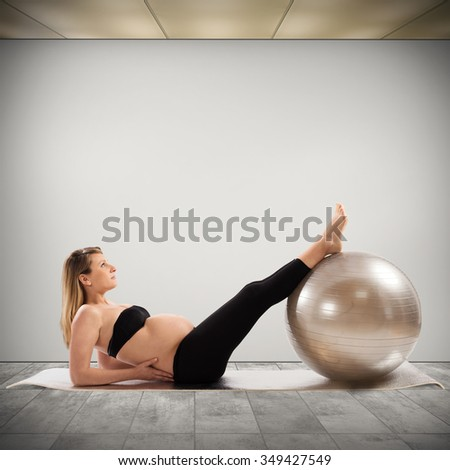 Pregnant woman does fitness exercises with ball - stock photo