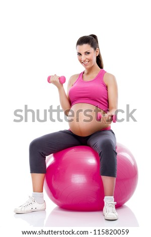 pregnant woman doing bicep muscle exercises using dumbbells while sitting on a fitness ball - stock photo