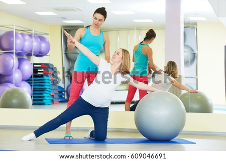 pregnant woman doing fitness ball exercise with coach