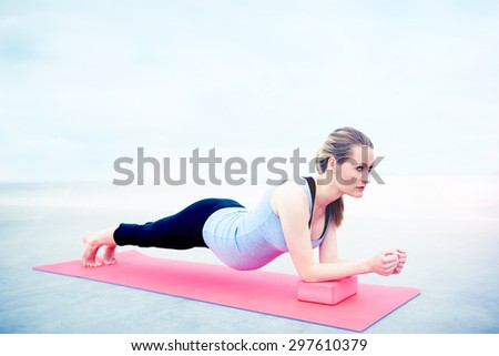 Pregnant woman doing fitness exercises to tone and strengthen her abdominal muscles working out on a gym mat balancing on her toes and elbows , with copyspace above - stock photo