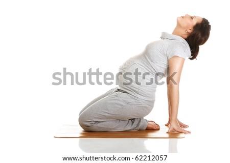 Pregnant woman doing gymnastic exercises on isolated white background - stock photo