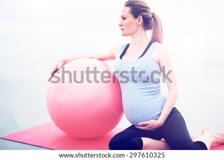 Pregnant woman doing pilates exercises to keep fit and tone her muscles sitting on a gym mat with a pilates ball looking to the side while supporting her swollen belly with her hand - stock photo