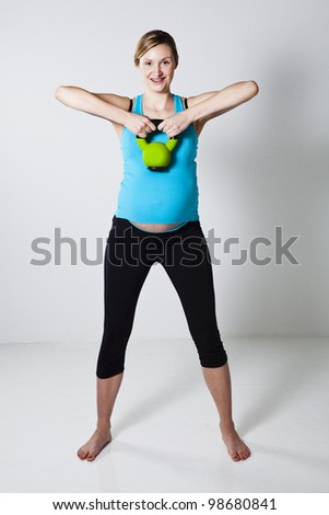 Pregnant woman doing shoulder muscle strengthening exercise with a kettlebell - stock photo