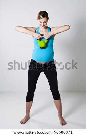 Pregnant woman doing shoulder muscle strengthening exercise with kettlebell - stock photo