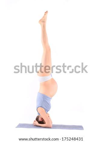 Pregnant woman doing yoga - stock photo