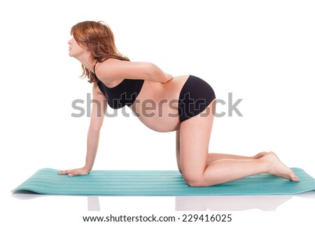 Pregnant woman doing yoga exercises. Isolated on white with wok path. - stock photo
