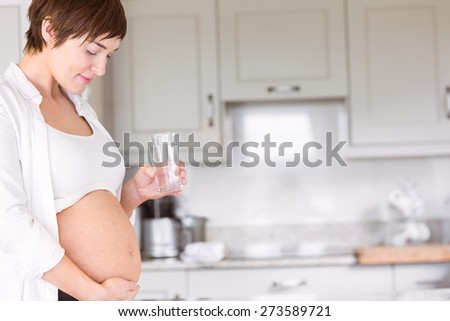 Pregnant woman drinking glass of water at home in the kitchen - stock photo