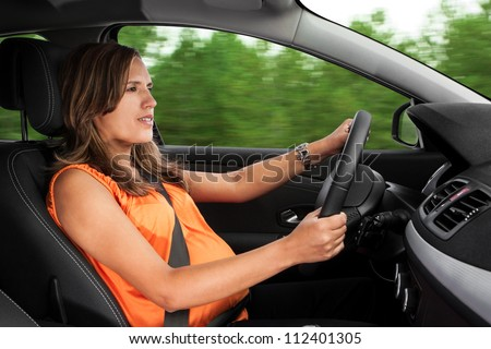 Pregnant Woman Driving Car Through the Woods - stock photo