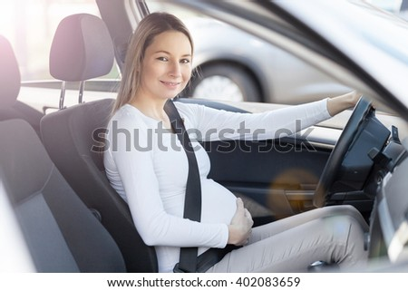 Pregnant woman driving her car, wearing seat belt - stock photo