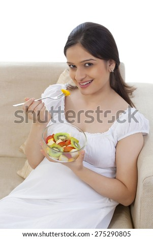 Pregnant woman eating fruits - stock photo