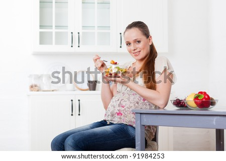 Pregnant woman eats fruit salad on the house kitchen. - stock photo