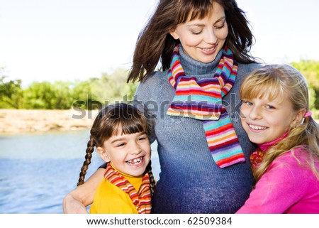 Pregnant woman embracing her daughters - stock photo