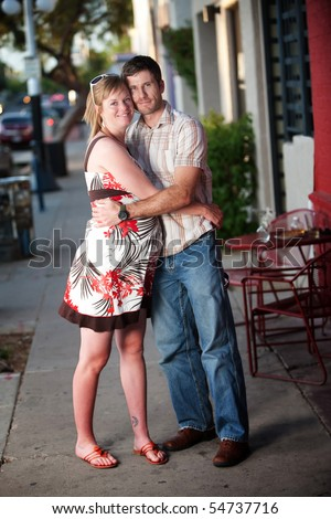 Pregnant woman embracing her partner outside of a cafe - stock photo
