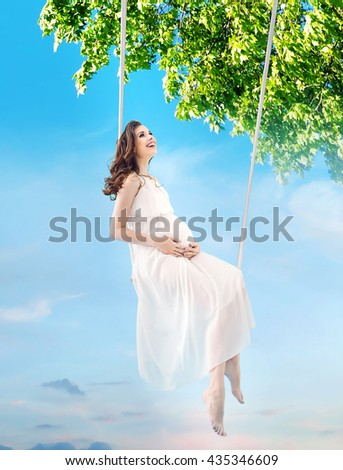 Pregnant woman enjoying summer park on a swing - stock photo