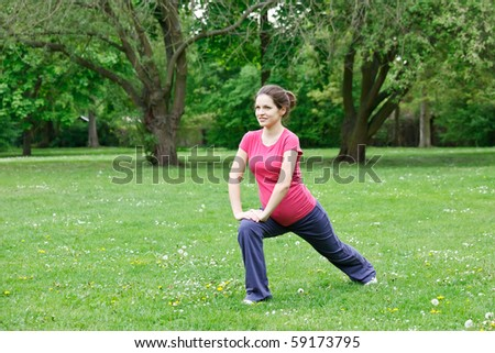 Pregnant woman exercising in the park - stock photo
