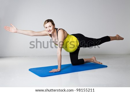 Pregnant woman exercising on mat to develop balance and muscular strength of the core trunk and shoulder muscles - stock photo