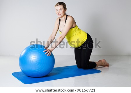 Pregnant woman exercising with a fitness ball on a mat - stock photo