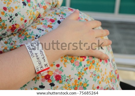 pregnant woman experiencing braxton hicks contractions in third trimester with twin on grounds of rbh - stock photo