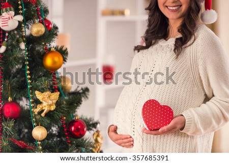 Pregnant woman happy at home near the Christmas tree during the Christmas celebration - stock photo