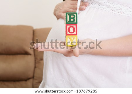 "pregnant woman having the word ""boy"" with wooden blocks written on her hand - stock photo"