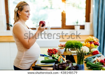 Pregnant woman healthy eating vegetables and fruit - stock photo