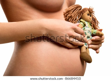 Pregnant woman holding a doll - stock photo