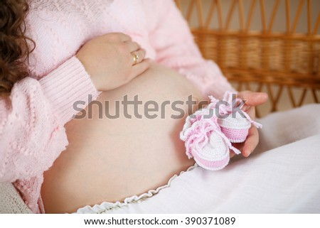 Pregnant woman holding a little knitted slippers in her hands