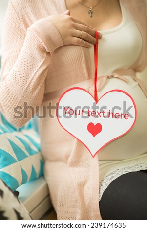 Pregnant woman holding a paper heart. - stock photo