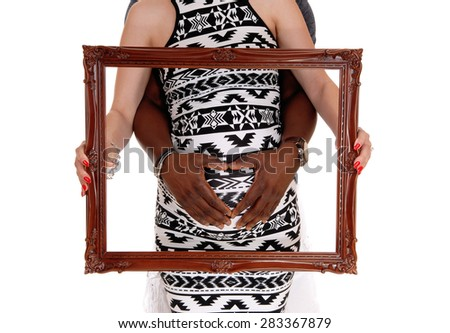 Pregnant woman holding a picture frame over her tummy and thehands of her African American man, isolated for white background. - stock photo