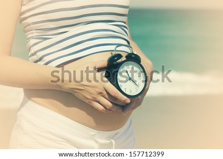 pregnant woman holding alarm-clock