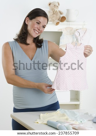 Pregnant Woman Holding Baby Clothes - stock photo