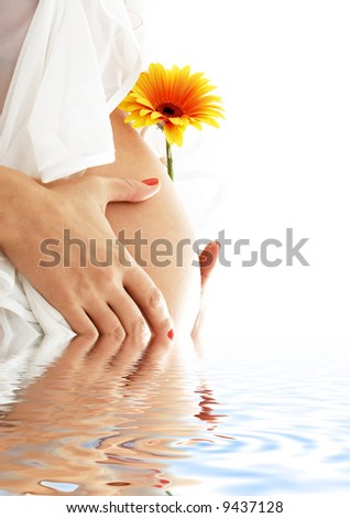 pregnant woman holding her belly and yellow flower in water