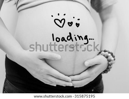 pregnant woman holding her belly it write word loading and draw heart in black and white mode. - stock photo